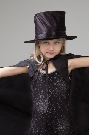 Adorable little girl wearing a black hat and cape looking at the camera close-up