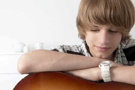 Portrait of Teenage Boy putting his hands on the guitar Looking thoughtfull Stock Photo