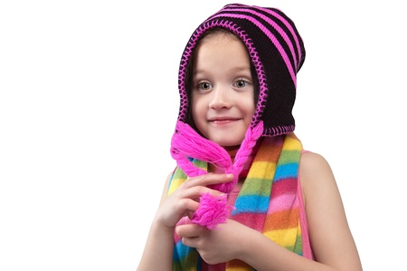 Smiling six year old girl in a colorful scarf and knitted hat  looking up standing on a white background Stock Photo - 16847980