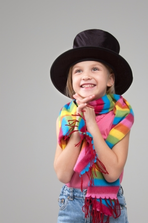 Smiling six year old girl in a black hat and a colorful scarf  looking up standing on a gray background Stock Photo - 16847982