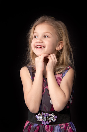 Smiling seven year old blonde girl in a dress looking directly standing put her hands to the face on a black background photo
