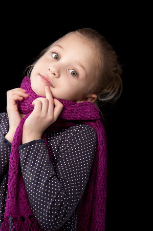 Seven year old blonde girl looking pensively in a scarf standing put her hands to the face on a black background photo