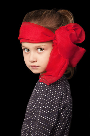 Seven year old blonde girl looking pensively in a red scarf standing on a black background photo