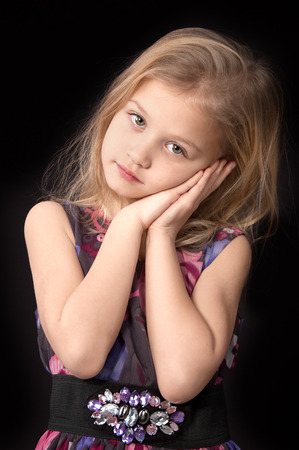 Seven year old blonde girl looking pensively in a dress standing  put her hands to the face on a black background photo