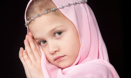 Seven year old blonde girl looking pensively in a pink scarf put her hands to the face on a black background Stock Photo