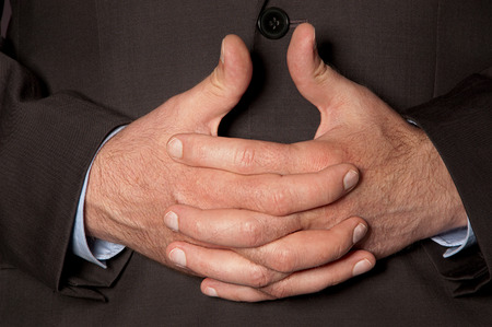 Man in suit clasped fingers in front of him closeup