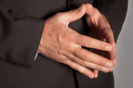Man in suit folded hands in as a pyramid closeup