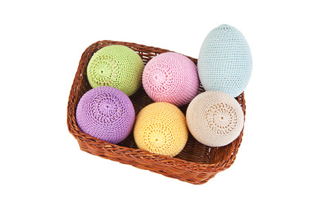 Colorful crocheted eggs in a wicker basket on a white background