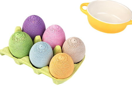 Colorful crocheted eggs in a light green carton egg box on a white background Banco de Imagens