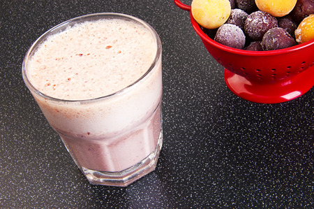 Cherry milk shake in a glass cup  and a red colander with frozen cherries and cherry-plum on a dark background