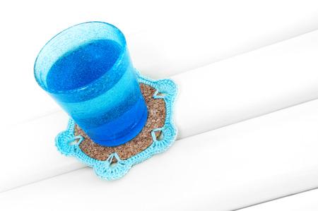 Blue glass on crochet blue coaster with cork base Stock Photo