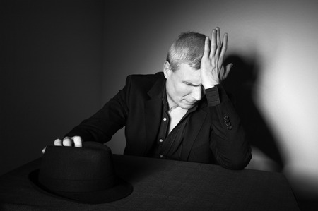 Man in black hat at the age of forty-six years old puts his hand on his hat and puts his hand to his forehead   on the background of a rough wall with texture Stock Photo