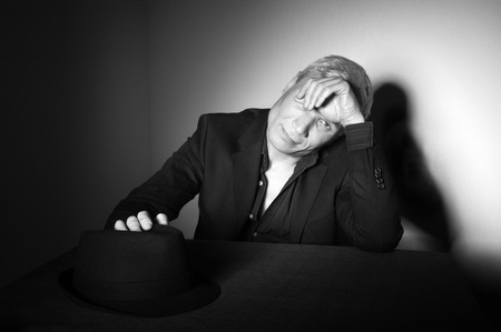 Man with  black hat at the age of forty-six years old put his hand on his hat and  hand covers one eye looking at the camera on the background of a rough wall with texture