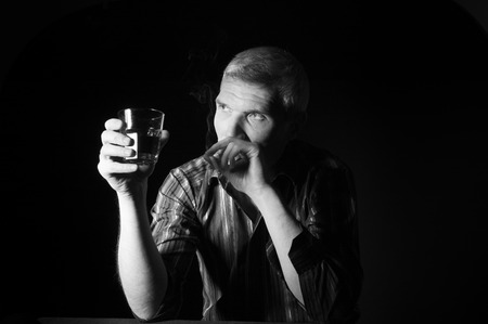 Man in a striped shirt at the age of forty-six years old holding a glass in his hand and smokes on the black background photo
