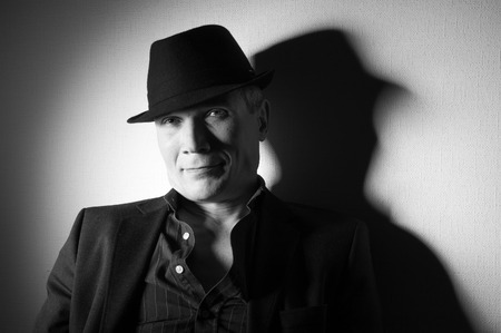 Man in suit and black hat at the age of forty-six years old looking at the camera  on the background of a rough wall with texture
