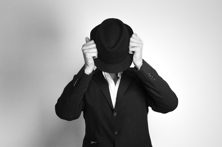 Man in suit and black hat at the age of forty-six years old lcovers his face with a hat on the background of a rough wall with texture Stock Photo