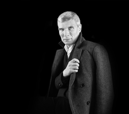 Man in coat at the age of forty-six years  looking at the camera  on black  background