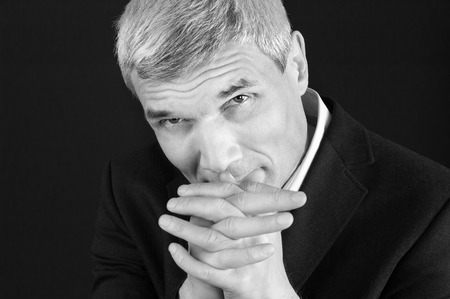 Grey-haired man in suit at the age of forty-six years old  with hands to head support  looking at the camera on black background