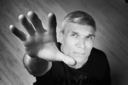 Grey-haired man in black T-shirt at the age of forty-six years old  with hand  looking at the camera  Stock Photo