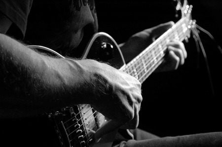Man with guitar in a black T- shirt at the age of forty-six years old playing guitar on a black background