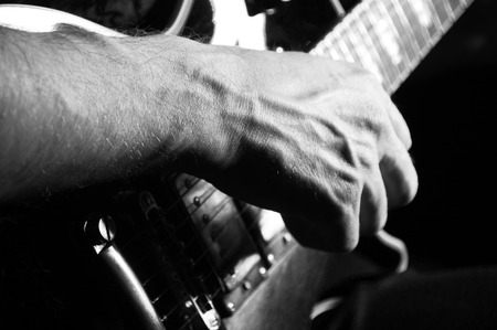 Man  playing guitar on a black background closeup Stock Photo