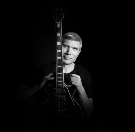 Man with guitar in a black T- shirt at the age of forty-six years old looking at the camera on a black background Stock Photo