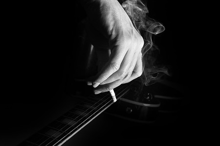 Composition of guitar and mans hand with cigarette smoking on black background