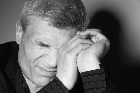 Grey-haired man in a suit at the age of forty-six years old hands covers one eye on the background of a rough wall with texture