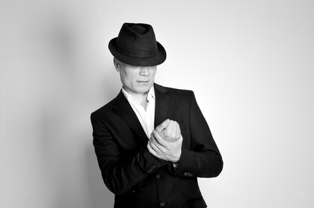 Man in suit and black hat at the age of forty-six years old looking at his hands on the background of a rough wall with texture