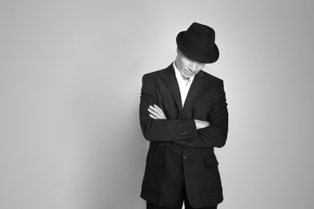 Man in suit and black hat at the age of forty-six years old looking down on the background of a rough wall with texture Stock Photo