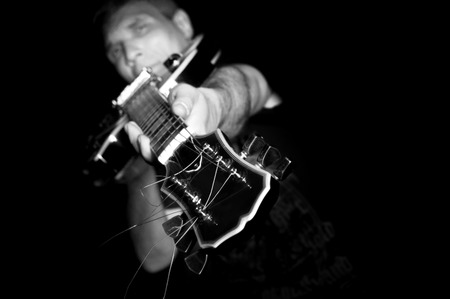 Man with guitar in a black T- shirt at the age of forty-six years old directs the guitar fretboard at the camera on a black background