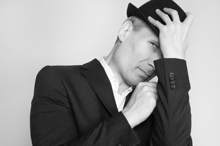 Man in black hat at the age of forty-six years old  looking at the camera on the background of a rough wall with texture Stock Photo