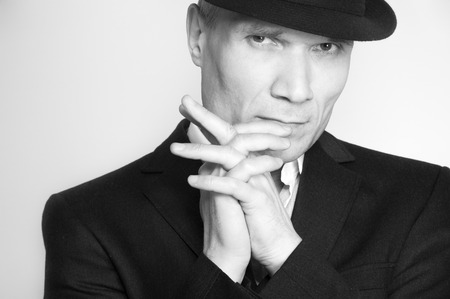 Grey-haired man in hat and suit at the age of forty-six years old  with hands to head support  looking at the camera on black background