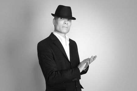 Man in suit and black hat at the age of forty-six years old  looking at the camera on the rough wall with texture Stock Photo