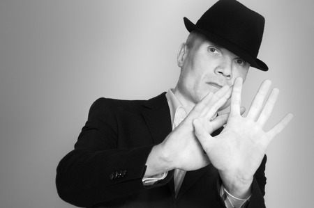 Man in suit and black hat at the age of forty-six years old  looking at the camera on the  rough wall with texture