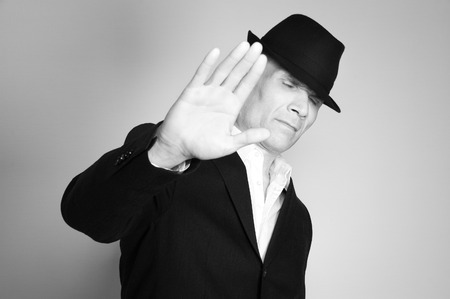 Man in suit and black hat at the age of forty-six years old with his eyes closed on the rough wall with texture