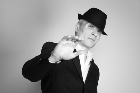 Man in suit and black hat at the age of forty-six years old  looking at the camera on the background of a rough wall with texture Stock Photo