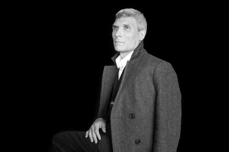 Man in coat at the age of forty-six years on black  background