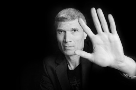 Grey-haired man in suit and  black T-shirt at the age of forty-six years old  with hand  looking at the camera on a black