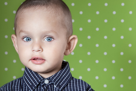 Surprised a little boy at the age of two in a shirt on light green background