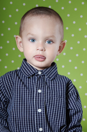 Surprised a little boy at the age of two in a shirt on light green background  looking at the camera close-up