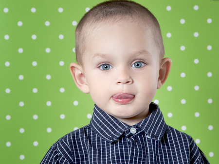 Adorable a little boy at the age of two in a shirt on light green background  looking at the camera close-up