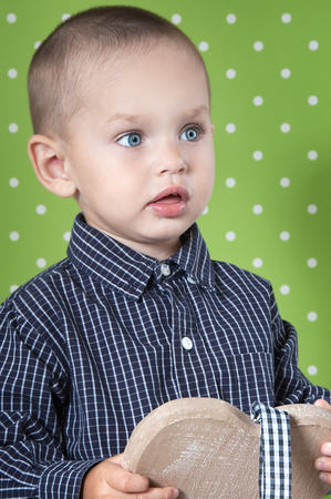 Surprised a little boy at the age of two in a shirt on light green background  holding a wooden heart  close-up Stock Photo
