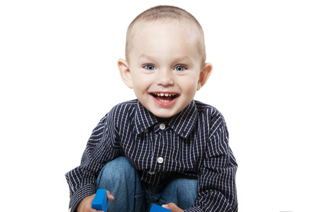 Smiling  little boy at the age of two in a shirt and jeans on white background playing cubes looking at the camera Stock Photo