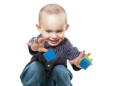 Adorable  little boy at the age of two in a shirt and jeans on white background throws the cubes