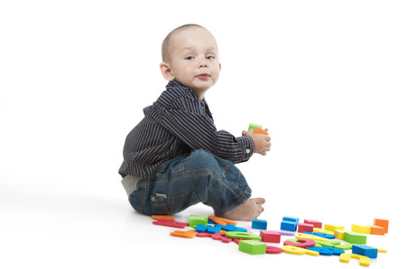 Adorable little boy at the age of two in a shirt and jeans sitting and looking at the camera on a white background with colorful letters and cubes