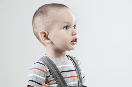 Adorable  little boy at the age of two in a striped T-shirt on a light gray background