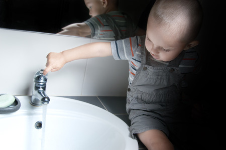 Adorable  little boy at the age of two in a striped T-shirt  looking at the flow of water in the sink