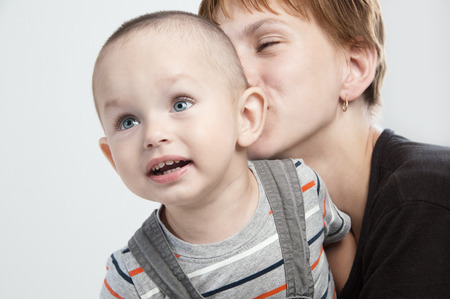 Adorable  little boy at the age of two in a striped T-shirt with his mother on a light gray background