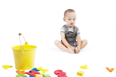 Sad  little boy at the age of two in a striped T-shirt  sitting and looking down on a white background with yellow bucket and colorful letters and cubes
